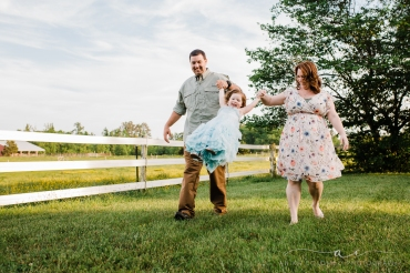 parents swinging toddler by the arms as they walk through a field, photographed by anika colombo photography