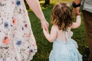 toddler walking away from camera holding both of her parents hands wearing a blue doll cake dress, photographed by anika colombo photography