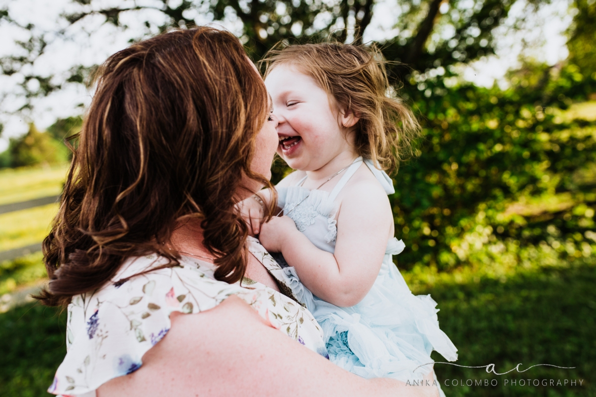 mother kissing daughter on the nose while child laughs, photographed by Anika Colombo Photography
