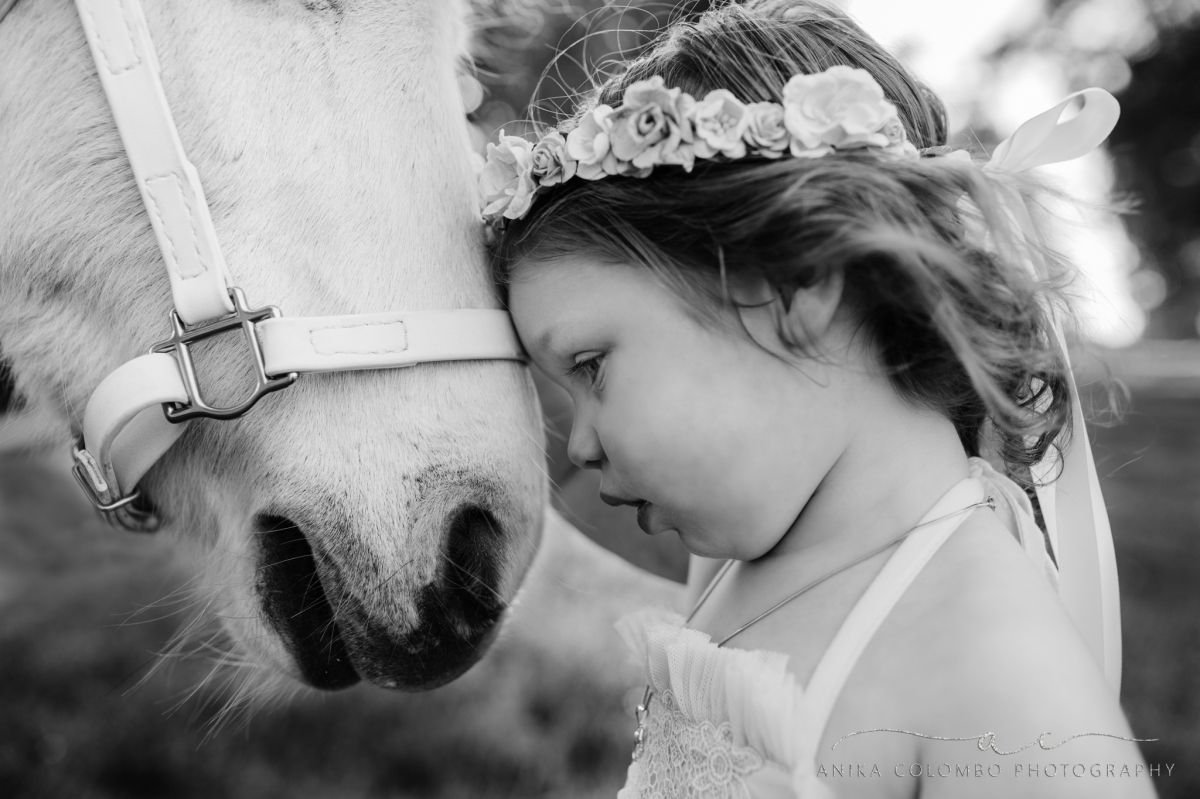 black and white image of little girl resting her forehead against a unicorn's nose
