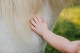 toddler putting her hand against a white unicorn