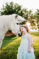 toddler putting her cheek against a white unicorn