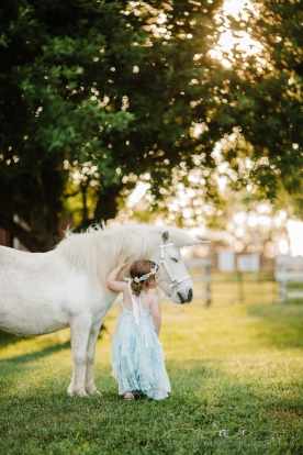 child standing in a field under a tree facing away from the camera while petting a sleepy unicorn