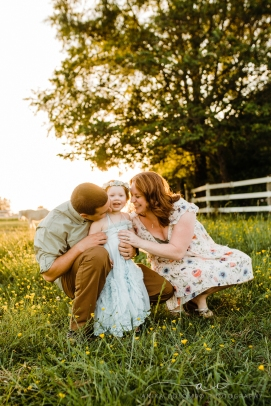 toddler staring into he camera as parents tickle and laugh at her in a field