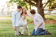 two teenage brothers kneeling on the ground tickling their little sister