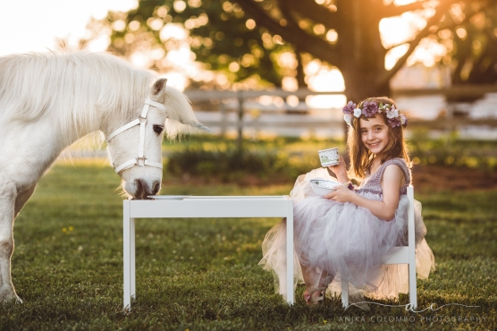 little girl wearing big tulle dress and flower crown having a tea party with a white unicorn and smiling at the camera with teacup in hand, photo by Anika Colombo Photography