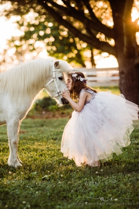 little girl in big tulle dress and flower crown leaning forward and kissing the nose of a white unicorn