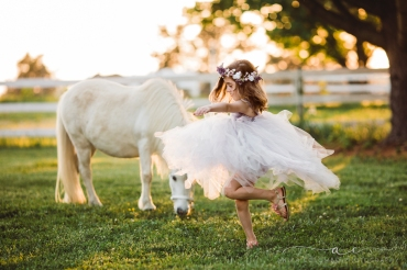 little girl wearing big tulle dress and flower crown twirling in the foreground with a white unicorn in the background, photo by Anika Colombo Photography