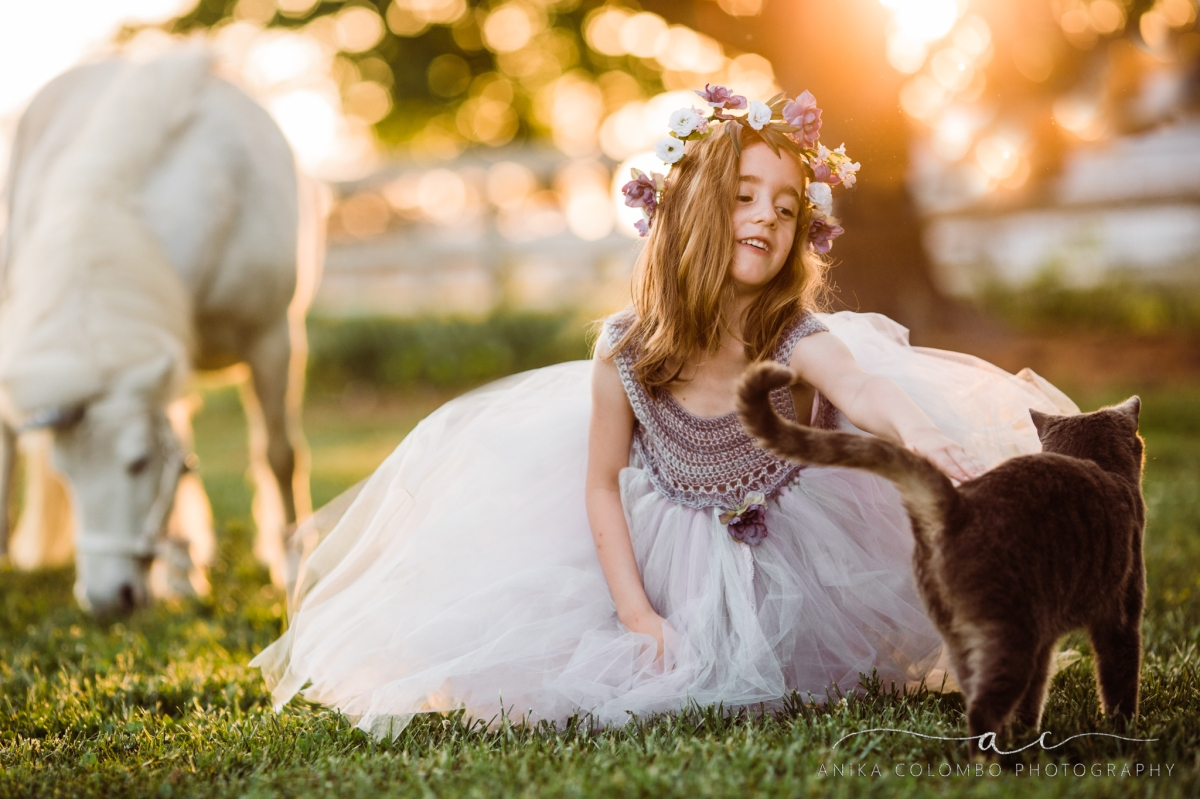 little girl wearing big tulle dress and flower crown sitting on the ground petting a cat with a white unicorn in the background, photo by Anika Colombo Photography