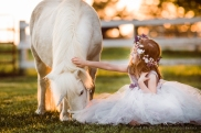 little girl wearing big tulle dress and flower crown sitting on the ground petting a white unicorn, photo by Anika Colombo Photography