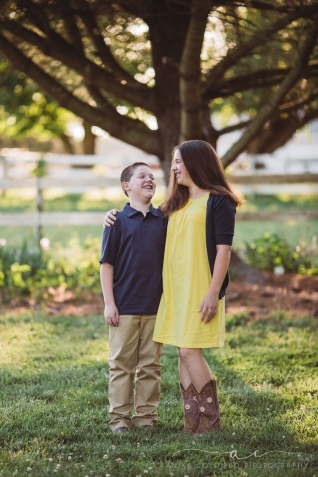 Siblings standing in front of a tree with arms around each other looking at each other and laughing