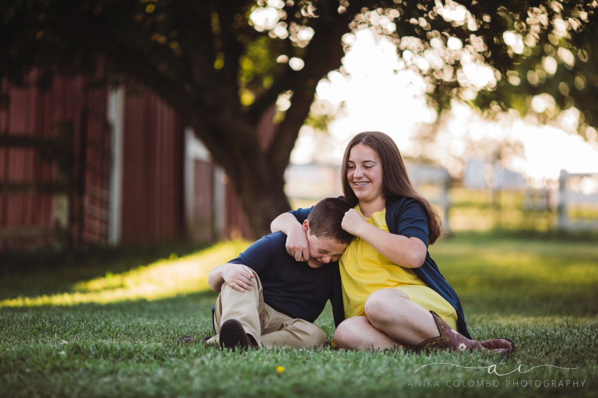siblings sitting in front of a tree and red barn, laughing while older sister gives younger brother a noogie