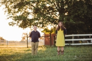 brother and sister standing in a field with their arms crossed behind their backs staring solemnly into the camera