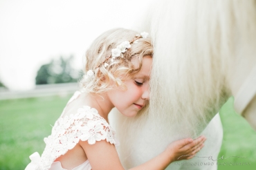 little girl wearing pink dress and floral crown hugging the neck of a white horse