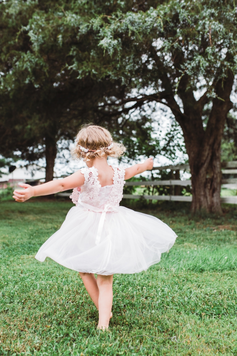 little girl wearing pink dress and floral crown twirling in a forest