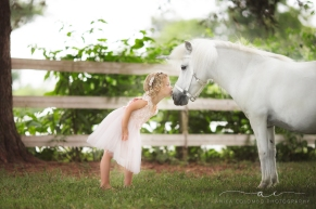 little girl wearing pink dress and floral crown leaning forward and kissing the nose of a unicorn