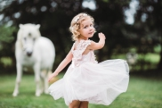little girl wearing pink dress and floral crown twirling with a white unicorn in the background