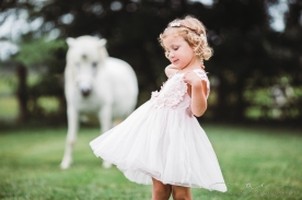 little girl wearing pink dress and floral crown twirling with a unicorn in the background