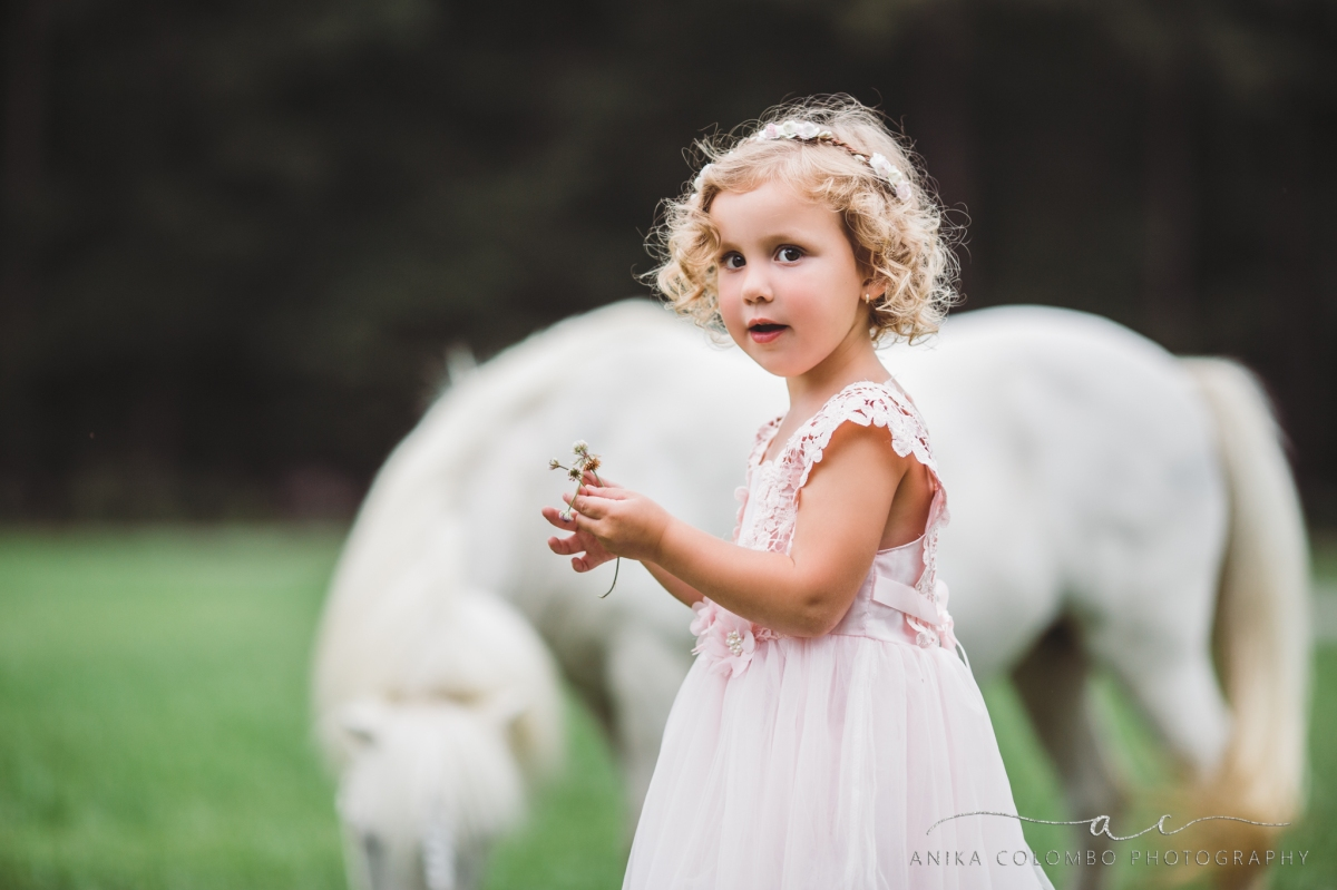 little girl wearing pink dress and floral crown picking flowers in front of a unicorn
