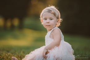 toddler sitting in the grass wearing pink tutu and headband staring into the camera