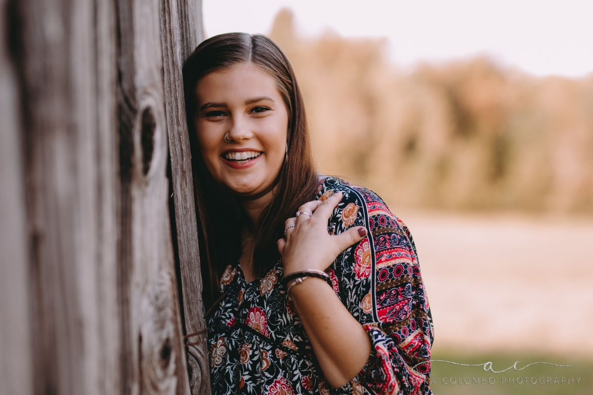young girl leaning against an old wooden barn laughing at the camera