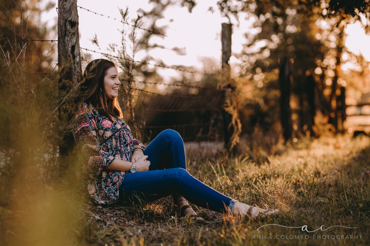 young girl in a field against a fence smiling into the distance