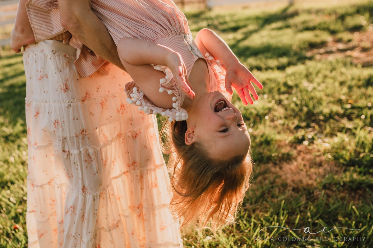 mother flipping daughter upside down, daughter laughing with excitement