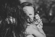daughter hugging mother's neck and smiling at the camera through her hair