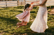 mother swinging daughter around by her hands in a sun drenched field