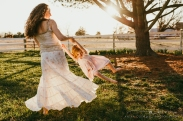 mother swings daughter around with flowing skirts in a field at sunset