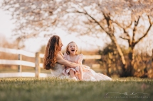 mother sitting holding young daughter in a pasture in front of a cherry blossom tree, daughter laughing