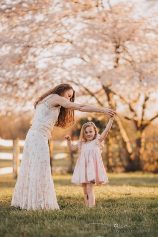 Mother twirling daughter in front of a cherry blossom tree