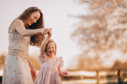 Mother twirling daughter while they both smile