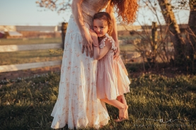 mother hugging daughter as she looks into the camera