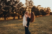 mother holding daughter in a field at sunset, daughter is laughing