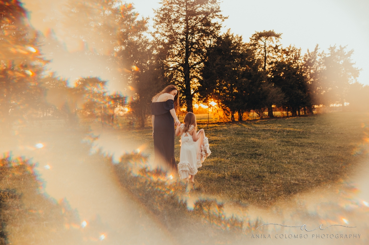 woman wearing long dress walks hand in hand with her young daughter wearing a pink dress through a field at sunset