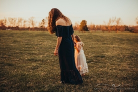 mother walks hand in hand with young daughter in a field at sunset