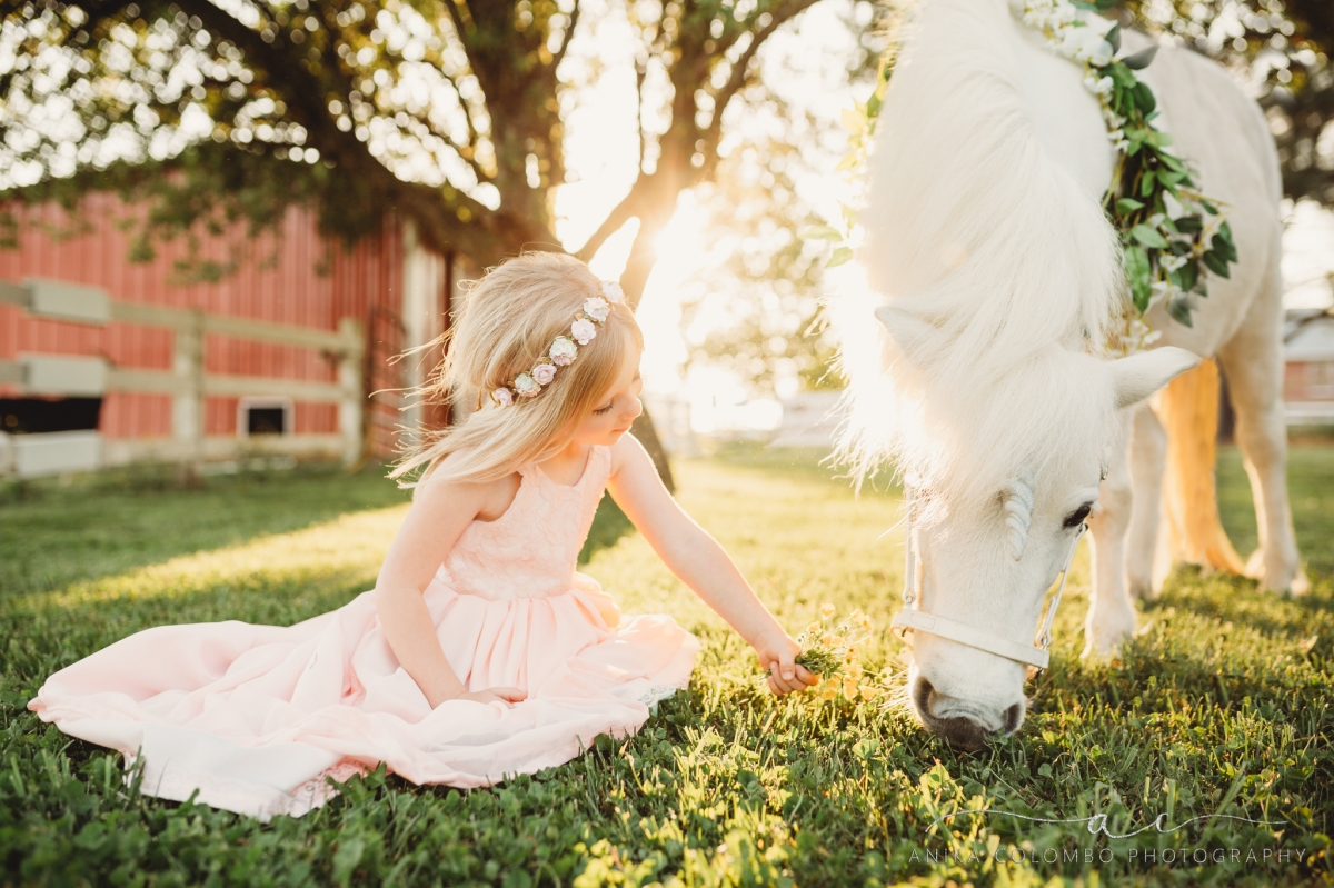 little girl sitting in a field under a tree petting a unicorn