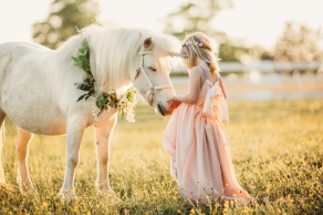 little girl in a field petting a unicorn