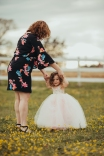 mother twirling daughter in a tutu in a field of buttercups