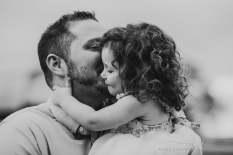 father kissing his daughter on the cheek