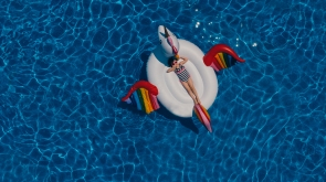 aerial view of child on a unicorn float in a pool