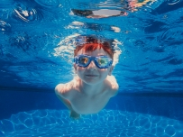 child swimming in the pool with goggles