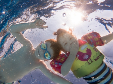 underwater image of kids looking at the camera and smiling