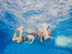 underwater image of kids swimming away and kicking their feet