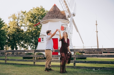 man twirling a woman in a long dress in front of a windmill