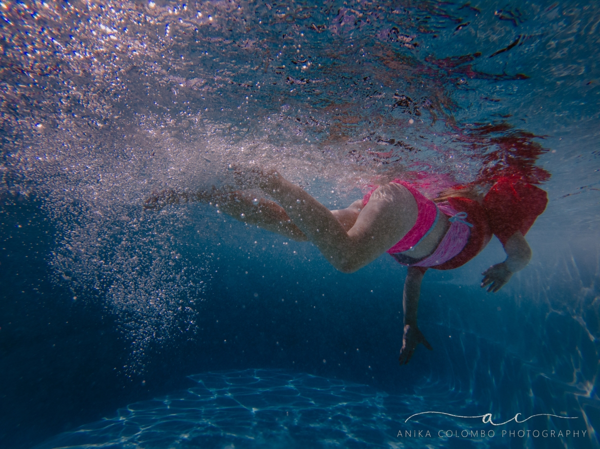 little girl swimming underwater kicking her feet with bubbles