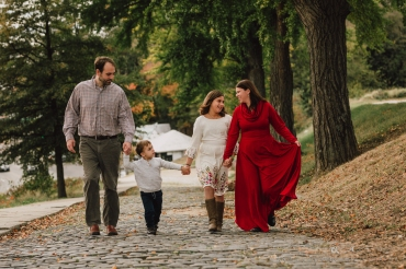 family walking on cobblestone street in richmond va holding hands and laughing