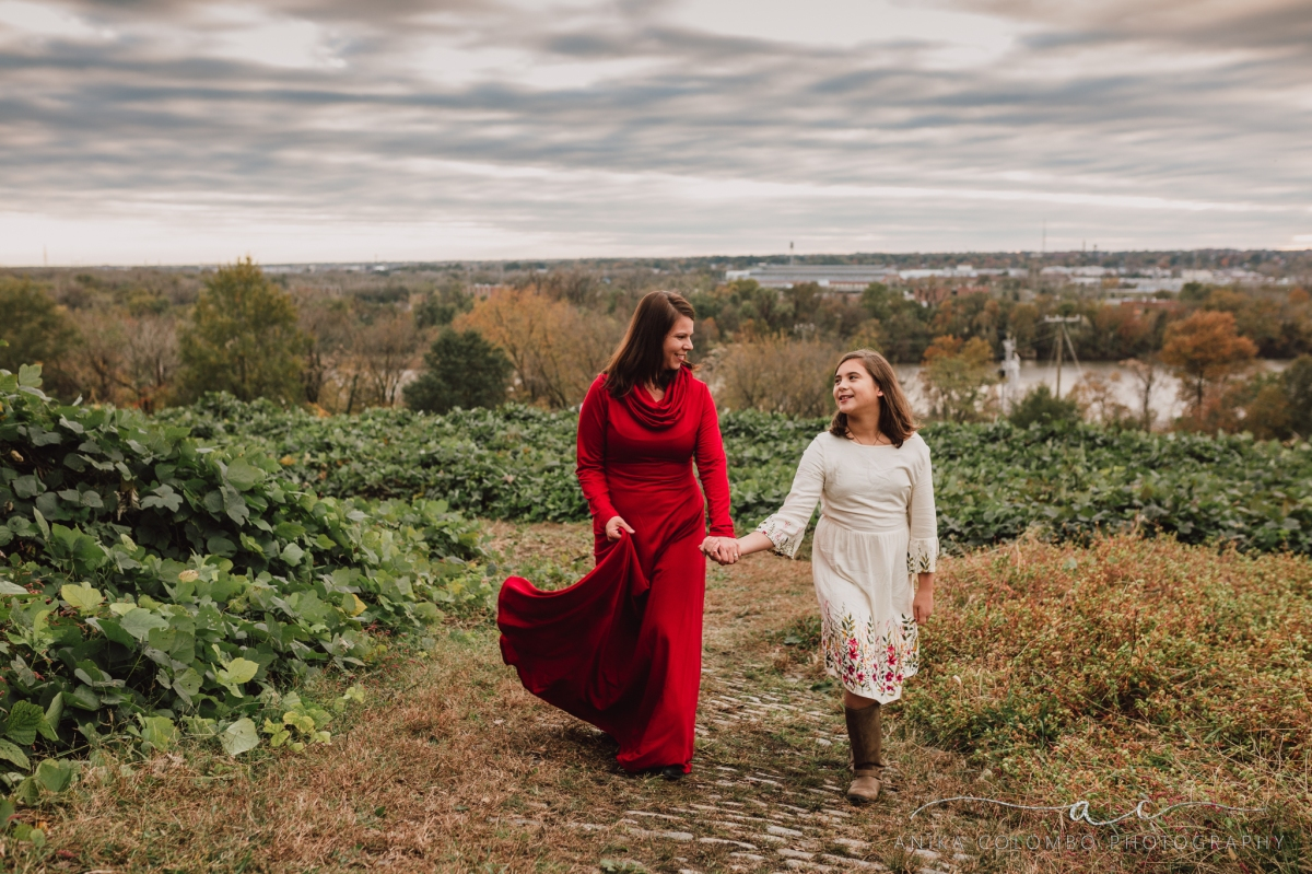 mother and daughter walking through a field over a hill in richmond va looking at each other and laughing