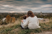young girl with her arm around her younger brother sitting on a hilltop looking over the city of richmond in va